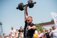 Strongmanen lyfter den tunga hanteln med en hand på konkurrenser, Ukraina, 2017 Royaltyfri Fotografi