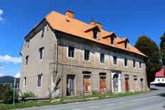 Stronniczo zniszczony zaniechany duża rodzina dom z łamanymi okno i rdzewieć rollup storami na drzwiach wspinał się na obdrapanym obrazy stock