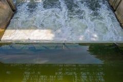 Stroom die door een waterkering in zonlicht vloeien Royalty-vrije Stock Afbeeldingen