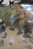 Stroom die over een kleurrijke rots stromen stock foto