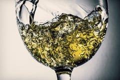Stroom van het witte wijn gieten in een glas, het witte close-up van de wijnplons Zwart-witte foto met kleur van wijn royalty-vrije stock foto
