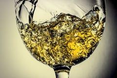 Stroom van het witte wijn gieten in een glas, het witte close-up van de wijnplons Zwart-witte foto met kleur van wijn stock foto's