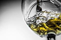 Stroom van het witte wijn gieten in een glas, het witte close-up van de wijnplons Zwart-witte foto met kleur van wijn royalty-vrije stock afbeeldingen