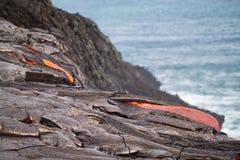Stroom van roodgloeiende lava in Vreedzame Oceaan stock foto