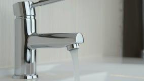 Stroom van water het gieten van chroom geplateerde tapkraan stock videobeelden