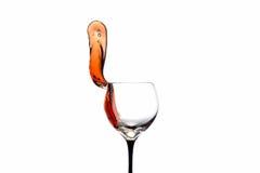 Stroom van wijn die van een geïsoleerd glas worden uitgegoten Royalty-vrije Stock Foto