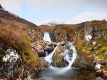 Stroomversnelling in kleine waterval op stroom, Higland in Schotland een vroege de lentedag Sneeuwbergpieken Royalty-vrije Stock Afbeelding