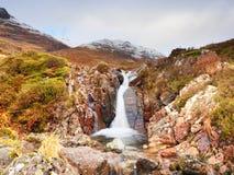 Stroomversnelling in kleine waterval op stroom, Higland in Schotland een vroege de lentedag Sneeuwbergpieken Stock Afbeelding