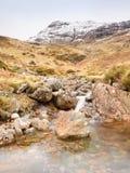 Stroomversnelling in kleine waterval op stroom, Higland in Schotland een vroege de lentedag Sneeuwbergpieken Stock Fotografie