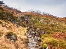 Stroomversnelling in kleine waterval op stroom, Higland in Schotland een vroege de lentedag Sneeuwbergpieken Stock Foto's