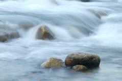 Stroomwater die voorbij stenen stromen royalty-vrije stock foto's