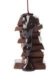 Stroop die op chocoladestukken wordt gegoten Stock Afbeeldingen