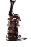 Stroop die op geïsoleerder chocoladestukken wordt gegoten Stock Foto