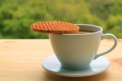 Stroopwafel alto chiuso disposto sopra la tazza di caffè caldo è servito sulla tavola di legno, fogliame verde vago nel fondo fotografia stock libera da diritti