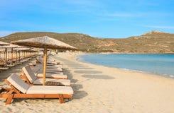 Stroparaplu's en sunbeds, aquamarijnoverzees en zacht wit zand van mooi Simos-strand, Elafonisos-eiland, de Peloponnesus, Grieken Stock Afbeelding