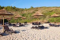 Stroparaplu's in het strand stock afbeeldingen