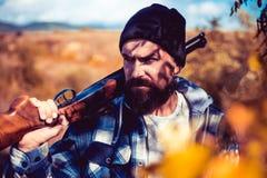 Stroper in het Forest Bearded-de holdingskanon van de jagersmens en het lopen in bos de Jachtvergunningen Jager met jachtgeweerka royalty-vrije stock afbeelding