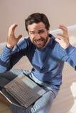 Strssed man sitting on floor using laptop Stock Image