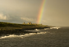 Struck by a rainbow. Dunstanburgh castle struck by a rainbow stock images