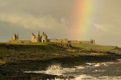 Struck by a rainbow 2. Dunstanburgh castle struck by a rainbow royalty free stock photography