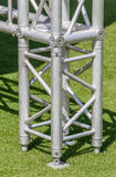 Structural detail of a lighting post base on green grass. Royalty Free Stock Photo