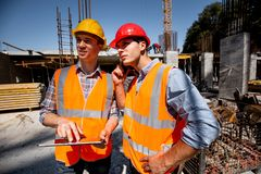 Structural engineer and architect dressed in orange work vests and hard bats discuss the construction process by the royalty free stock photography
