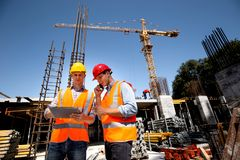 Structural engineer and architect dressed in orange work vests and hard hats discuss the construction process by the stock image