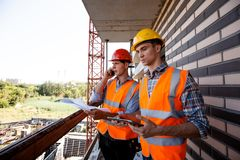 Structural engineer and architect dressed in orange work vests and helmets discuss the construction process, use a phone stock photo