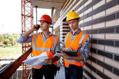 Structural engineer and architect dressed in orange work vests and helmets discuss the construction process, use a phone royalty free stock image