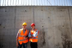 Structural engineer and architect dressed in orange work vests and helmets stand on a concrete wall background royalty free stock images