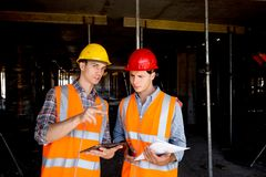 Structural engineer and architect dressed in orange work vests and helmets use tablet and keep project documentation stock images