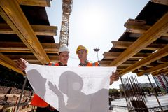 Structural engineer and architect dressed in shirts, orange work vests and helmets explore construction documentation on royalty free stock photos