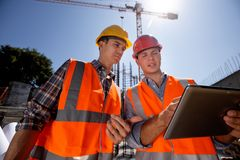 Structural engineer and construction manager in orange work vests and hard helmets discuss documentation and talk by stock photography