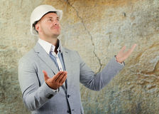 Structural engineer pleading ignorance. Or a large crack in a wall alongside him raising his hands to show he does not know what happened Royalty Free Stock Photo