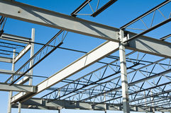 Structural steel construction. The structural steel structure of a new commercial building against a clear blue sky in the background Royalty Free Stock Images