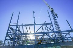 Structural steel framework for new building. White structural steel framework for new building against deep blue sky stock image