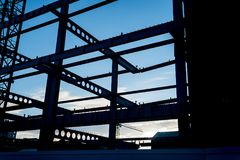 Structural steel girders framed in silhouette. Structural steel girders framed in silhouette as sun rises with blue sky through framing and shapes with black Royalty Free Stock Photography