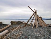 Structure de tipi de tipi de bois de flottage sur une roche Pebble Beach par l'eau sur le littoral photos stock