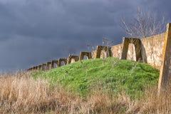 Structure en béton détruite d'une vieille ferme abandonnée sur un fond des nuages bleu-foncé Image stock