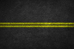 Structure of granular asphalt. Asphalt texture with two yellow line road marking. royalty free stock image