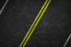 Structure of granular asphalt. Asphalt texture with two yellow line road marking. stock image