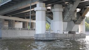 Structure of modern bridge. View on massive structure under bridge from passing boat stock video
