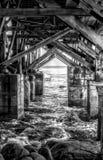 Structure noire et blanche sous le pilier avec l'océan et les roches image stock