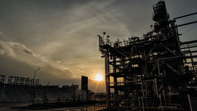 Structure of oil industry backlit by sunset Royalty Free Stock Images