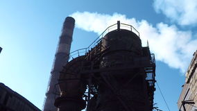 The structure of the steel plant on the background of the pipe from which goes white smoke stock video