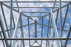 Structure of steel roof frame with blue sky and clouds Stock Photo