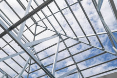 Structure of steel roof frame with blue sky at constr Royalty Free Stock Image