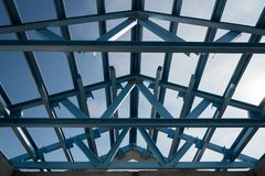 Structure of steel roof frame for building construction. Isolated on blue sky background royalty free stock photo