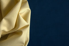 Structure of yellow cotton fabric on a blue fabric background Royalty Free Stock Images