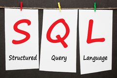 Structured Query Language SQL. Written on set stickers with clip hanging on a rope on black background stock photography
